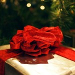 A gold wrapped present with a big red ribbon bow.