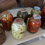Large canning jars filled with various fruits and vegetables.