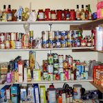 A well stocked pantry with several shelves filled with items.