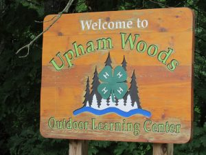 Wooden sign that reads Welcome to Upham Woods Outdoor Learning Center
